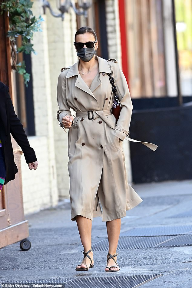 Stylish:The cover girl paired the impeccably elegant cover up with black sandals, adding a coordinating handbag she slung over one shoulder