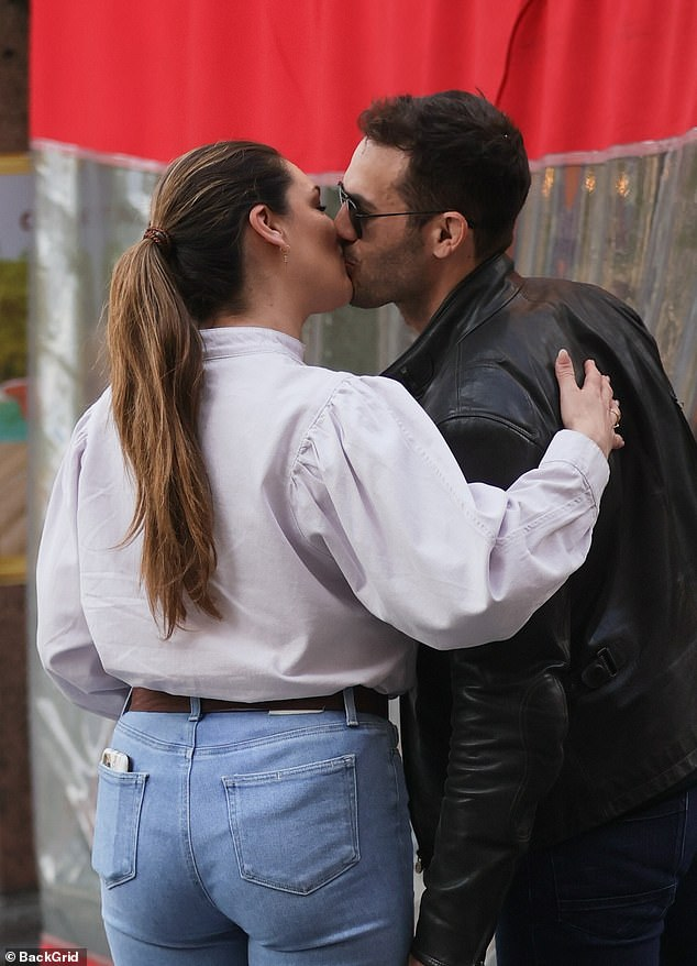 Loved up: Kelly Brook and boyfriend Jeremy Parisi couldn't keep their hands off one another as they were seen strolling in London on Wednesday