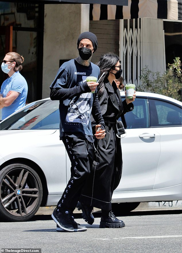 Lucky in love: The 42-year-old reality star cuddled up to Travis Barker while on a matcha run as sources told Entertainment Tonight that her famous family is 'in shock' over how different she is with a new love in her life