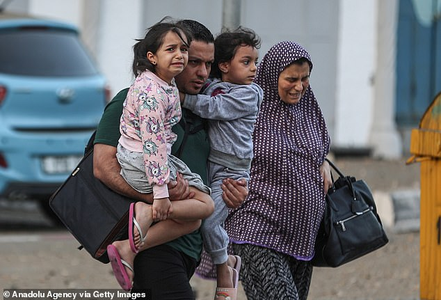Palestinians leave their neighborhood to head to a safer location on Wednesday in Gaza City