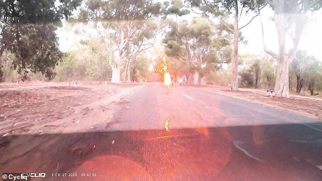 Multiple bright orange sparks of lightning flashed across the bitumen behind the bike riders