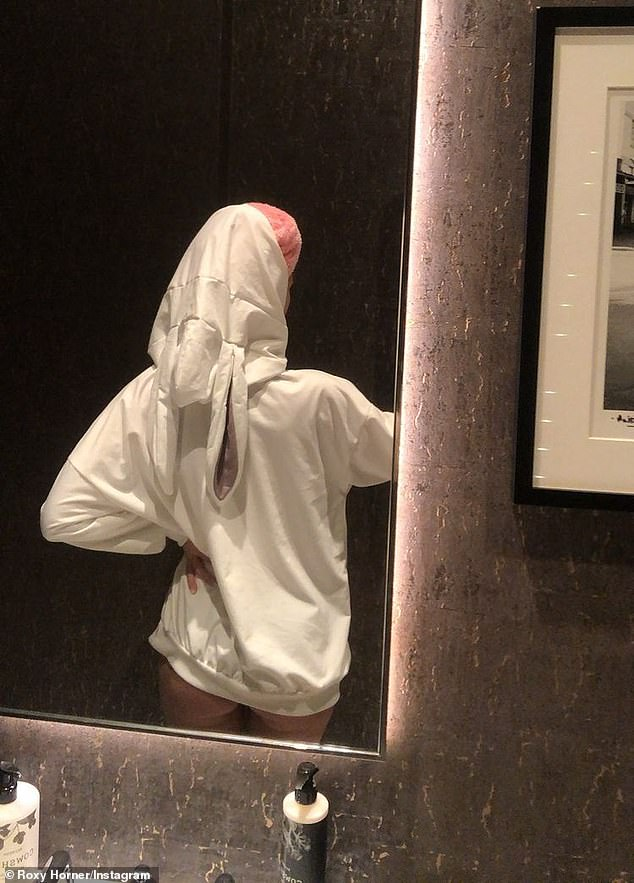 Cheeky: In a second sexy picture the blonde beauty flashed a hint of her peachy derriere in just the hoodie