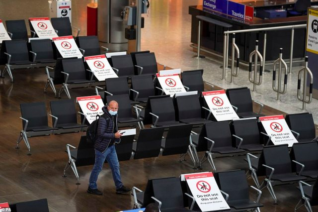 A passenger looks for a seat in the departures area in Terminal 5 at Heathrow Airport earlier today before next week's rush