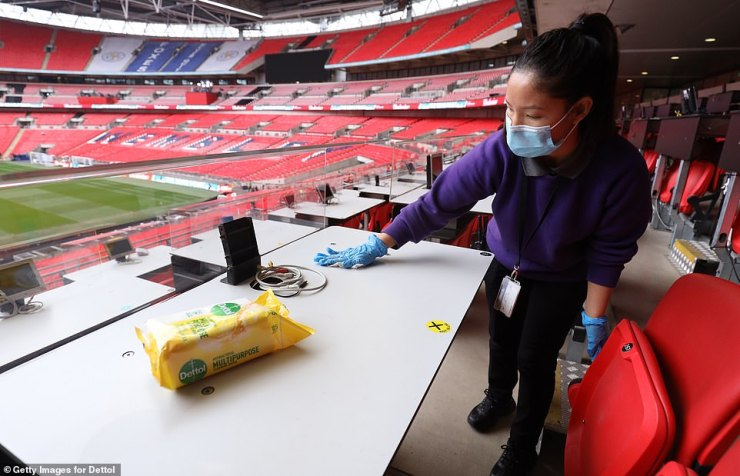 Surfaces in the press box at Wembley Stadium are wiped down with disinfectant ahead of Saturday's showpiece final
