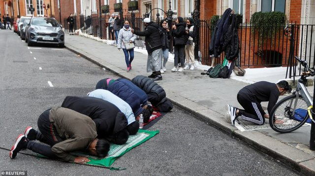 Muslims who attended the pro-Palestinian protest take a moment to pray in a street in Kensington