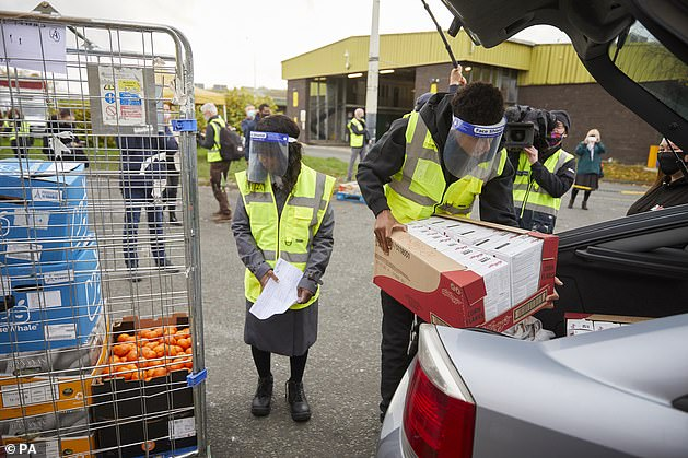 Helping: Marcus forced a Government U-turn on free school meal vouchers over the summer holidays (pictured FareShare Greater Manchester at New Smithfield Market with his mother)