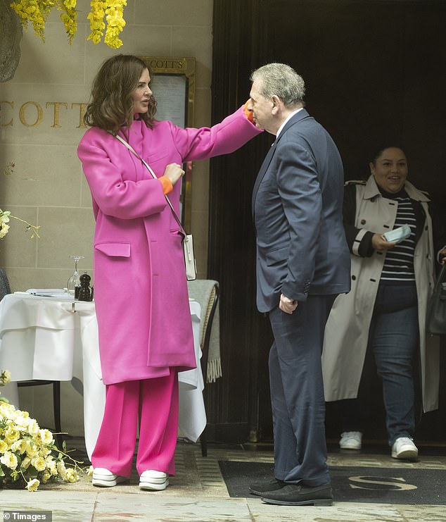 Close: The presenter, 57, brightened up the rainy day and looked effortlessly chic in a long fuchsia coat and matching pink trousers as she chatted with Charles outside the swanky eatery