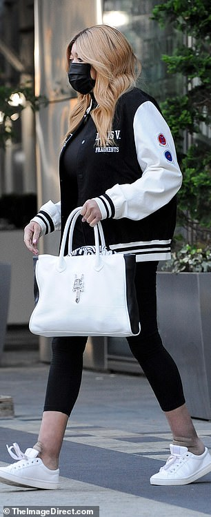 Continue: The media personality wore a white and black tote bag that complemented her monochrome outfit