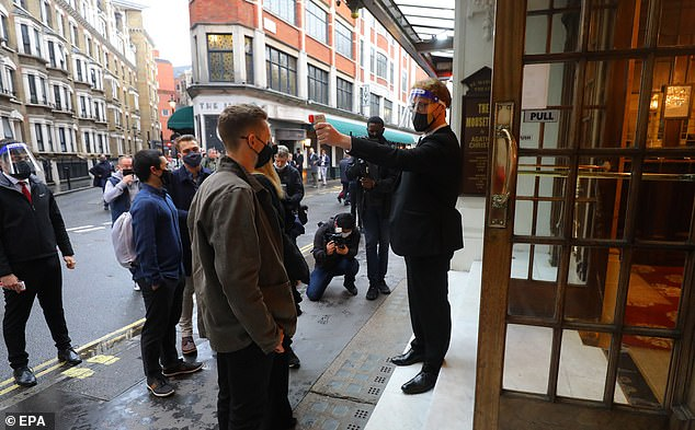 Theatergoers get their temperature checked upon arrival at St Martins Theater in London's West End