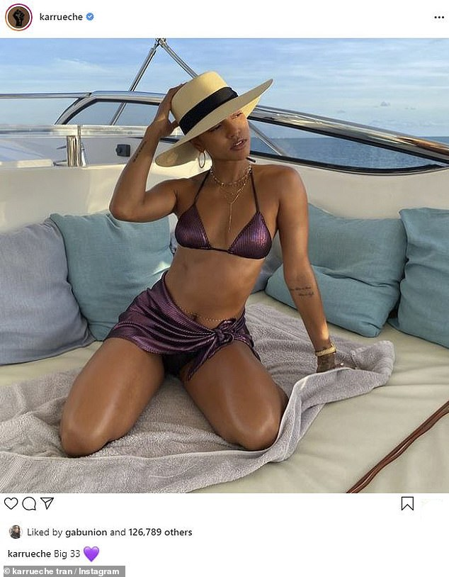Sizzling: Karrueche Tran posed a storm on a boat in a shiny purple bikini top and short skirts with a panama hat as she celebrated her 33rd birthday on Monday