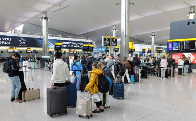Passengers queue up for check-in in the departures hall at London Heathrow Airport's Terminal 2 yesterday