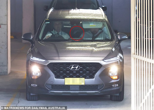 MacGill (pictured, sitting in the back seat)was driven away from his home at Cremorne to give a statement after four men were arrested in relation to his alleged kidnapping on May 5