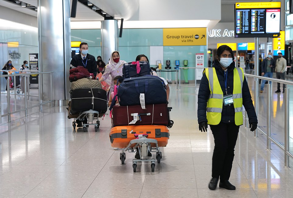 Passengers push their luggage as they walk through the arrivals hall at London Heathrow Airport's Terminal 2