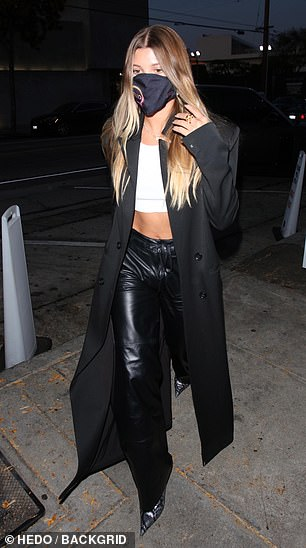 Strutting her stuff: She also wore black leather pants, pointy silver-snakeskin heels, and a black blazer-duster