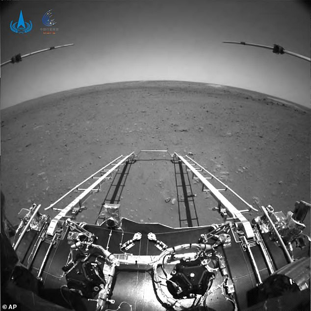 In this black-and-white front shot taken by China's Zhurong Mars rover and made available by the China National Space Administration (CNSA) on Wednesday, extension arms and a departure ramp are deployed on the rover's lander on the surface of Mars