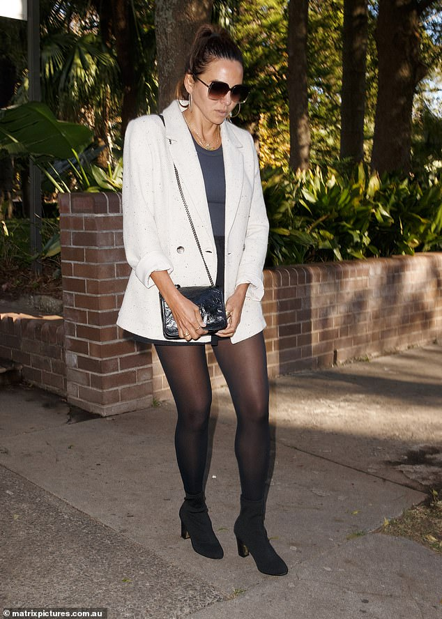 Fashionable arrival: Luciana opted for a grey sleeveless top, black high-waisted shorts, sheer black stockings and ankle boots. She added a tailored white blazer to the look