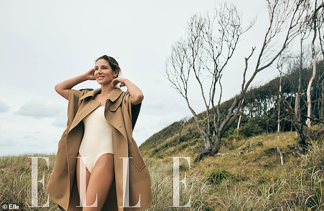 Strike a pose:She then changed in a stylish white swimsuit and a brown coat for a third image