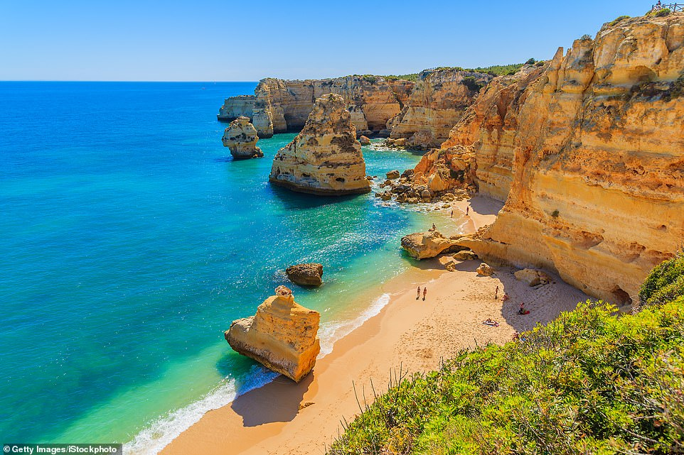 Freedom at last: The turquoise waters of Praia da Marinha in the Algarve. The region is known for its fine sand beaches, pretty villages and renowned golf courses