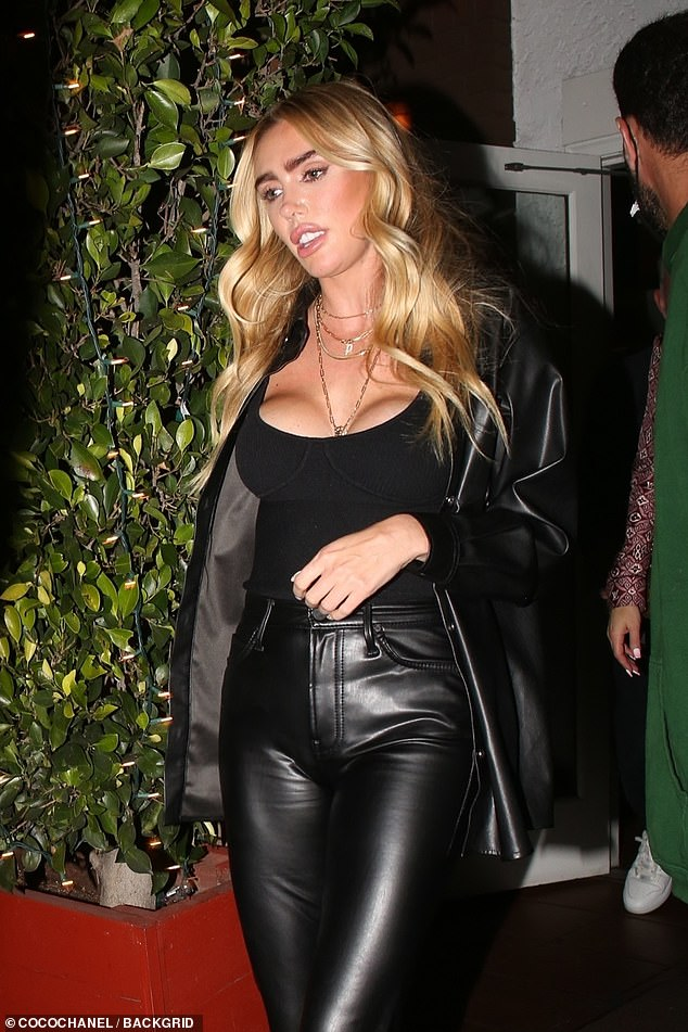 Stylish:Petra looked typically stylish in leather-look trousers and a matching oversized jacket as she rang in the weekend