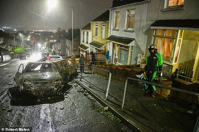 Two cars are seen with severe fire damage on the street. The tarmac has also been damaged with the heat of the blaze