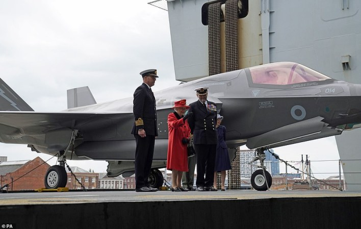 She wore a red outfit and hat as she was seen smiling with ship commanders in front of one of the F35B stealth fighter jets