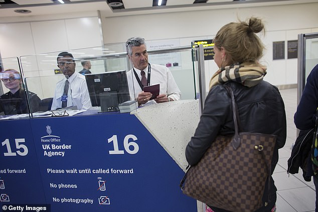Border Force officers are pictured checking passports of passengers arriving at Gatwick Airport