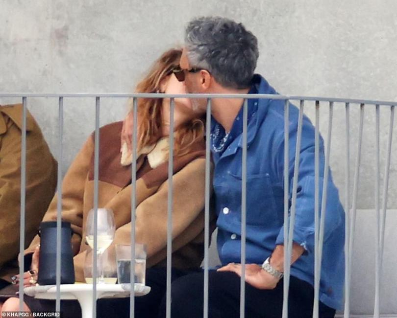 Locking lips: Rita and Taika could not resist sharing kisses as they chatted to other pals outside