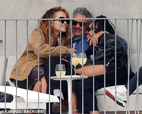 Beaming: Tessa could not stop smiling as she cosied into Taika and laughed across him with Rita