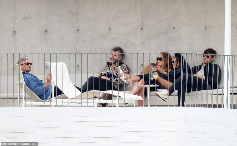 Swapping seats: Taika moved around during the festivities, enjoying a smoke on his white lounger at one point