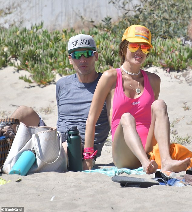 Low-key: Richardused a Big Asia cap and cycling sunglasses to keep sun safe as he lazed on the beach with his girlfriend