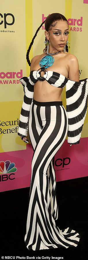 Straight out of Beetlejuice: Earlier in the evening, Doja sported another black and white ensemble
