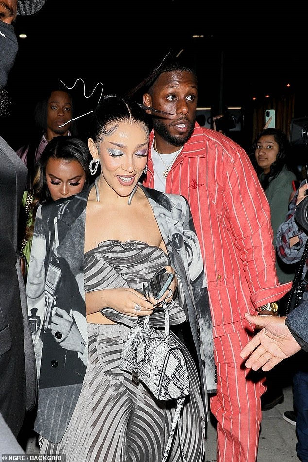 Chic: She clutched a snakeskin handbag