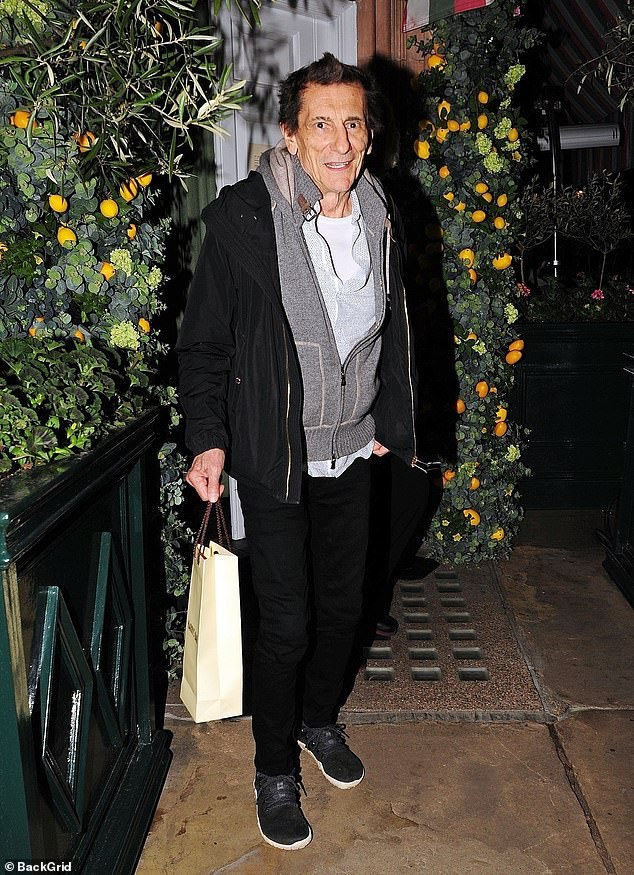 Casual cool:Ronnie cut a casual figure for his night on the town, layering a white T-shirt beneath a grey zip-up jumper and black coat