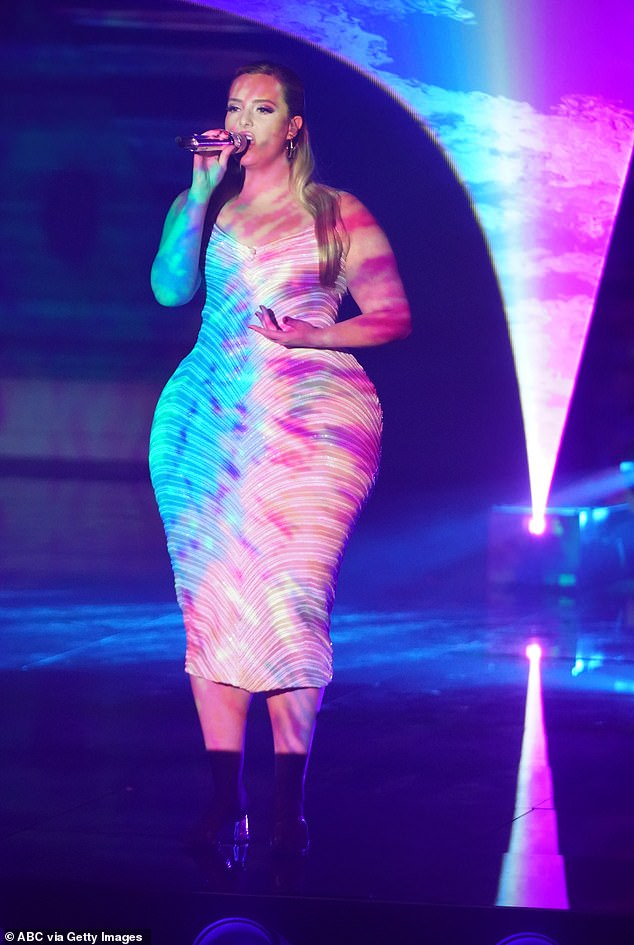 Fashion flare: The singer wore a white-patterned number for one song