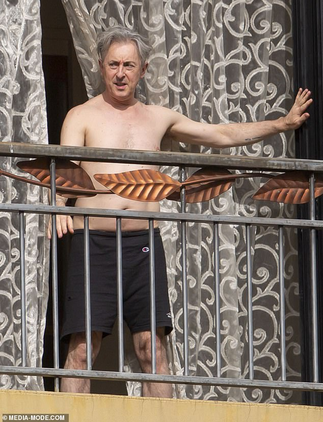 Soaking up the sun: Alan Cumming has been making the most of the sunshine on his balcony while in mandatory hotel quarantine in Adelaide