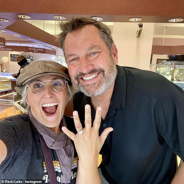 'He put a ring on it!' Ricki Lake reveals fiancé Ross Burningham has FINALLY given her a diamond sparkler in a Monday Instagram post... three months after getting engaged