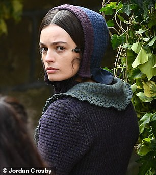 Look: Emma's brunette locks were styled into a slick bun with a middle parting, and her hair was partially covered with a knitted bonnet