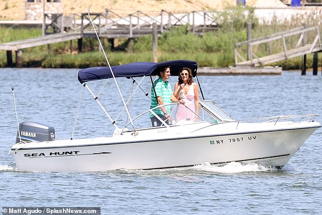 At sea:She wore a plunging pale pink floral dress that showed off her chest and toned arms as well as deep tan. The star added light rose colored sunglasses as she wore her hair down in loose curls