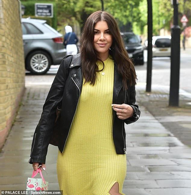 Gifts: She wore her brunette tresses were styled in a lose wave and she carried a birthday bag in her hand during the outing in Primrose Hill