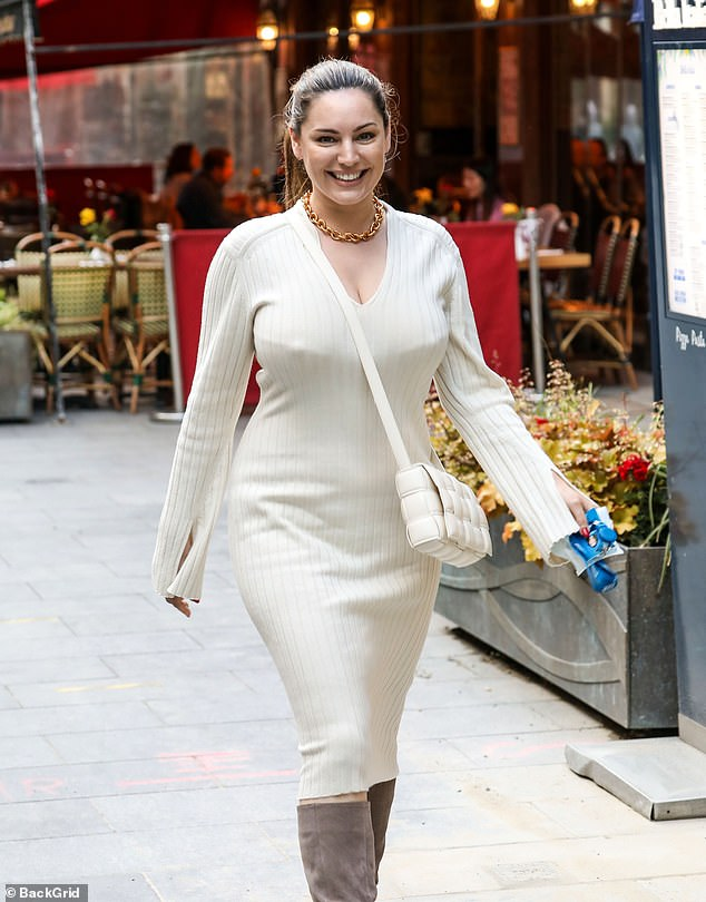 Beautiful: Kelly's figure-hugging dress, which had slits at the hands flashing a glimpse of her red manicured nails, showed off her sizzling hourglass shape