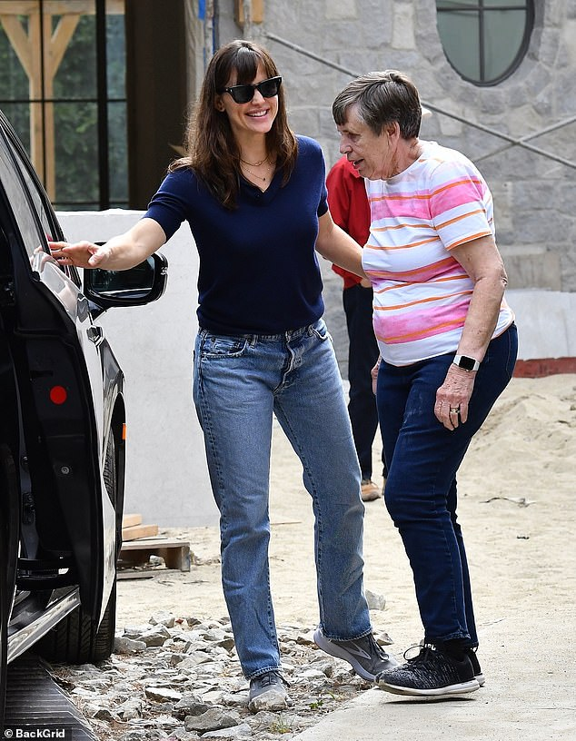 Smiley:Garner looked cheery as she smiled at passersby, while helping her mom into her black SUV