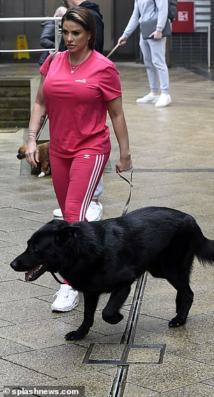 Laid back:Katie cut a casual figure for the day, donning a bright pink T-shirt with matching tracksuit bottoms with white stripes