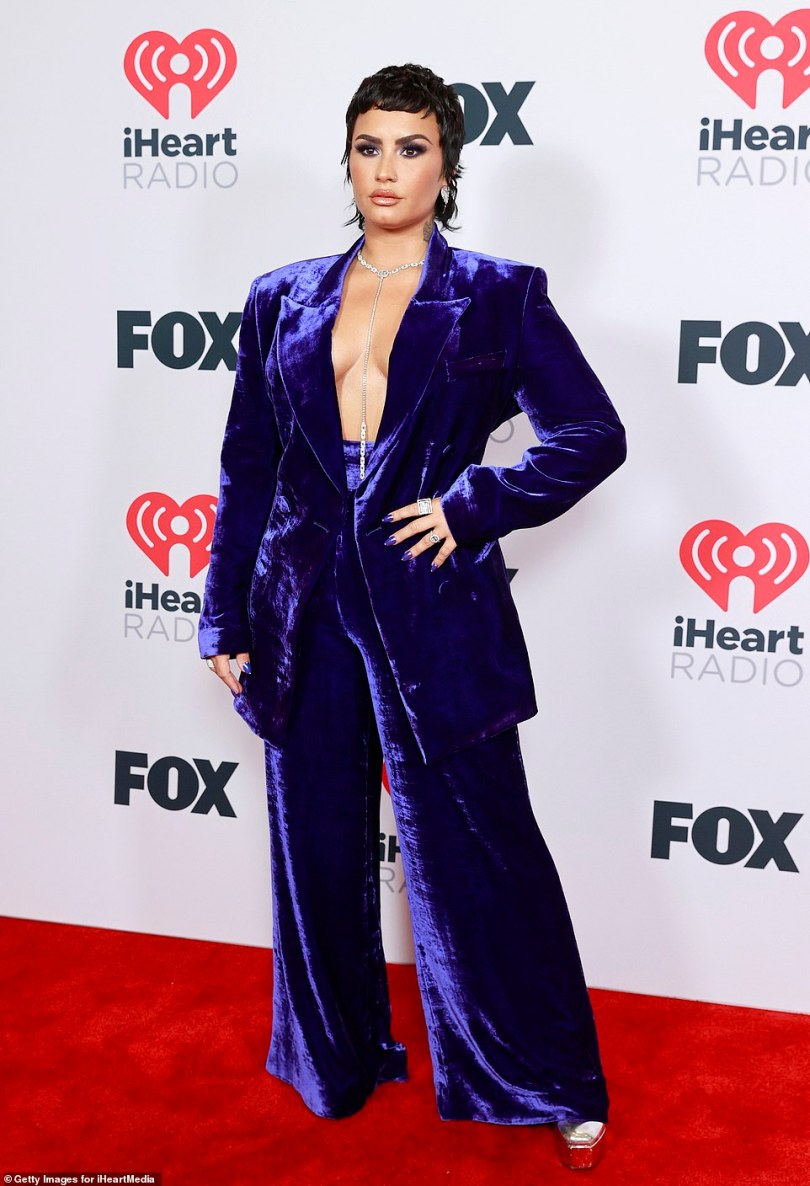 Wow!Demi Lovato wowed in a purple suit jacket and matching flared trousers, which appeared to be an homage to the night's iHeartRadio Icon Award recipient Elton John