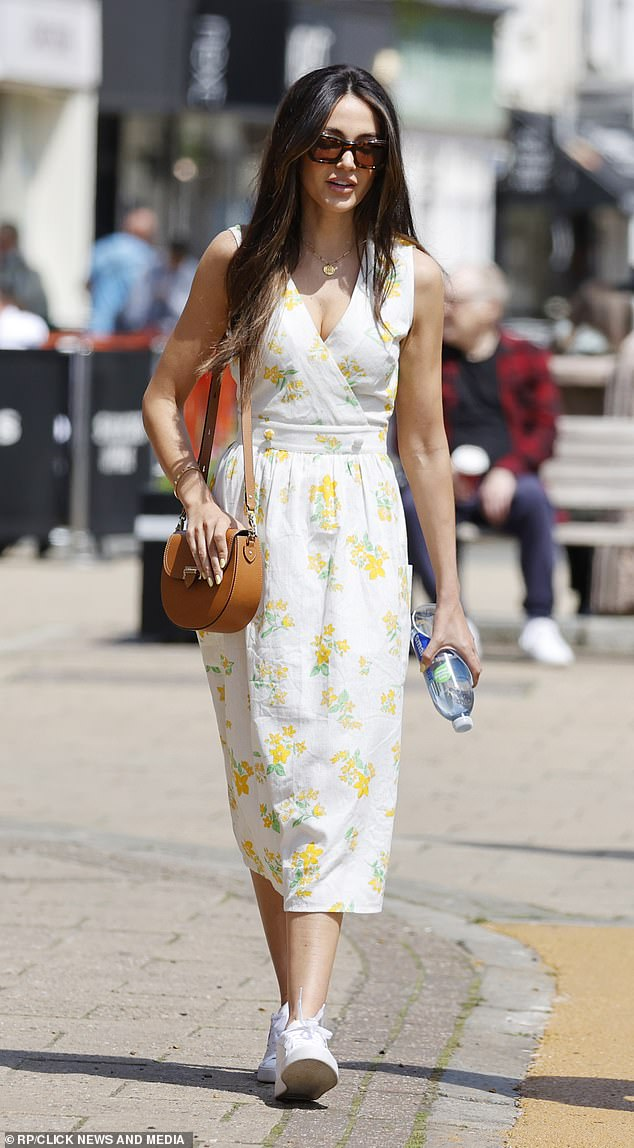 Chic: The brunette bombshell completed her outfit with a pair of plain white trainers and some small hoop earrings