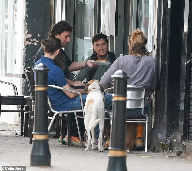 Group outing: James looked in good spirits as he joined his group at an al fresco meal