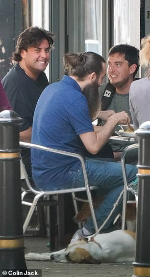 Having a laugh: The TV personality flashed a big smile as he joined his pals for breakfast