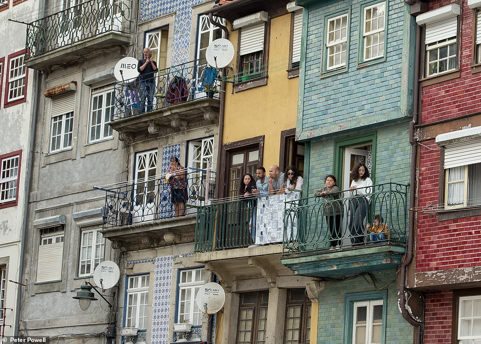 Porto locals stand on their balconies and watch on as English football fans enjoy themselves near the River Douro