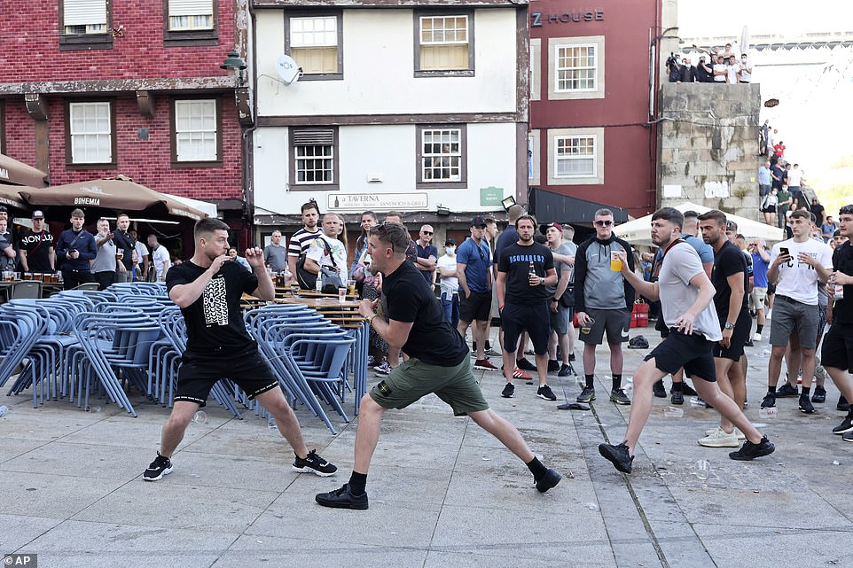 A fist fight starts among Manchester City supporters drinking by the Douro river bank in Porto, Portugal