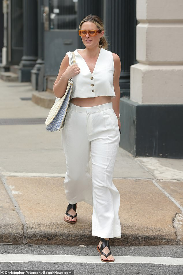 City chic: The 29-year-old, who has lived in the US for close to a decade,teamed a cropped vest with high waisted trousers and black leather sandals