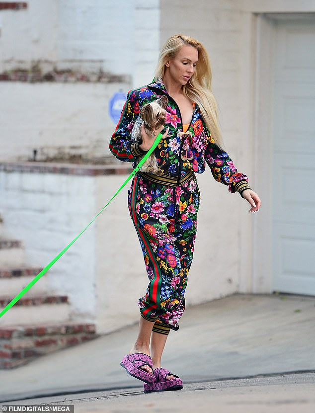 Chic: The new mother looked fresh faced for the makeup-free LA outing, carrying one pup under her arm while the other walked beside her on a neon green lead